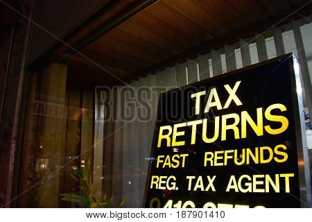 tax returns fast refunds with yellow lettering sign in anonymous shop window at night