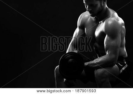 Black and white shot of a strong young muscular athlete exercising with dumbbells strengthening his biceps copyspace brutality confidence masculinity concentration focusing gym sports body muscles.