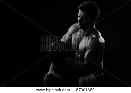 Monochrome low key light shot of a shirtless athletic man working out with dumbbells copyspace weightlifting bodybuilding toning fitness strengthen powerful brutal masculine concentrating sexy hot.