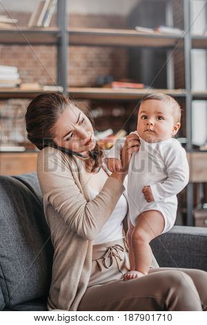 Portrait Of Cheerful Woman Talking On Smartphone And Spending Time With Her Son At Home