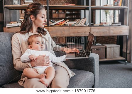 Concentrated Mother With Her Son Sitting On Couch And Using Laptop At Home. Home Business Concept