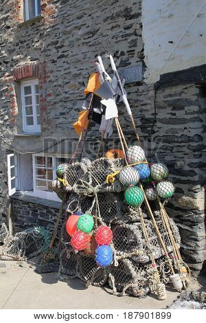 Lobster pots buoys and marker flags next to a stone house in a traditional English fishing port