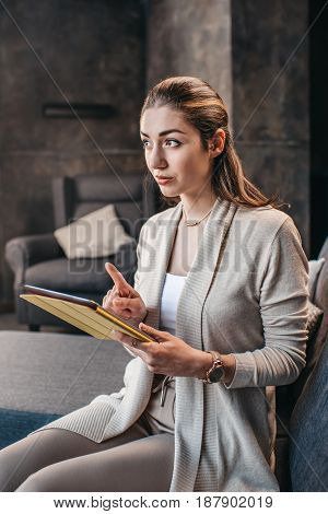 Portrait Of Attractive Woman Using Digital Tablet And Gesturing While Looking Away