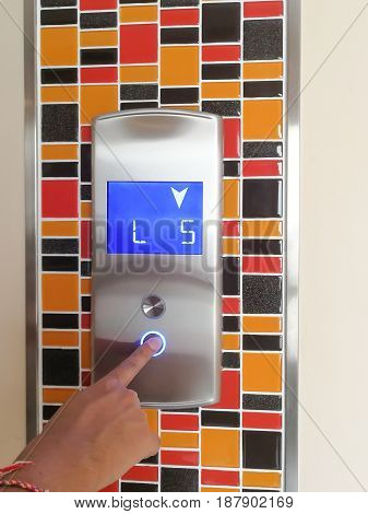 human hand pressing floor number of residential building and calling the elevator