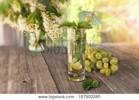 Detox water mint grape juice and ice in a glass on a background of a bouquet of cherry and grapes in a Sunny day.