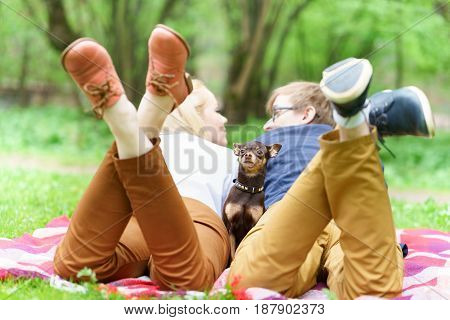 Young Attractive European Couple With Small Dog Between Them Is Getting Rest On Blanket In Some Summ