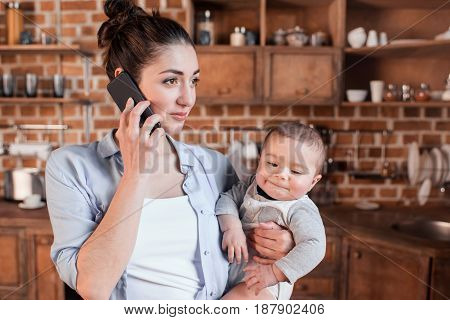 Portrait of young mother with baby boy in her arms talking on smartphone in the kitchen. Domestic life concept