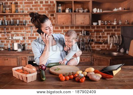 Portrait Of Mother With Son Talking On Smartphone And Preparing Dinner In The Kitchen