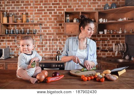 Happy Young Family Cooking Breakfast Together. Mother Chopping Cucumber On Cutting Board While Her S