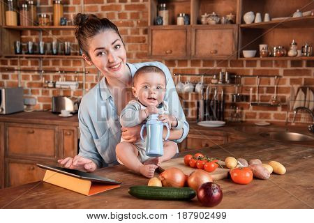 Portrait Of Young Mother With Her Little Son Cooking Dinner Together And Using Digital Tablet In The