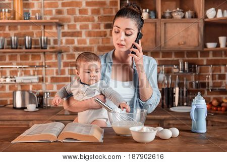 Young Mother Holding Her Son, Talking On Smartphone And Preparing A Dough In The Kitchen. Family Lif