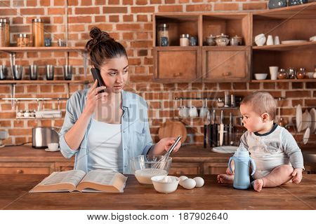 Young Mother Talking On Smartphone And Looking At Her Son During Cooking Dinner.
