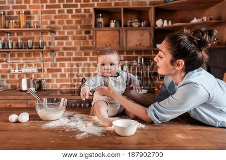 Happy Mother With Her Son Preparing Dough For Cookies And Having Fun Together At The Kitchen