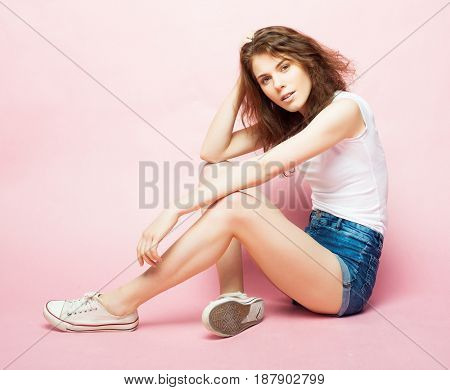 Full body portrait of a female fashion model sitting on pink background