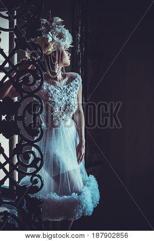 Young beautiful bride standing in the palace room.