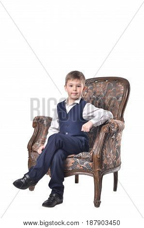 Schoolboy sitting in an antique-designed chair isolated on white background