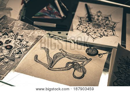 Time does not dominate over picture. Various sketches of tattoos locating on desk in salon. Close up