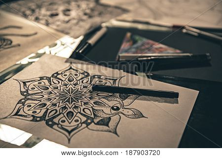 Extraordinary calligraphic ornament with markers situating on table. Picture concept. Close up