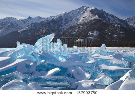 Blue ice hummocks on snowy mountains background