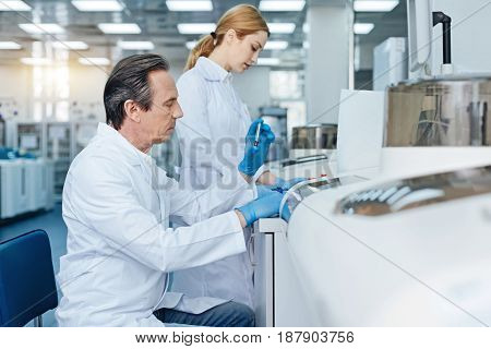 Seriousness at work. Gray-haired male person sitting in semi position and raising left hand while looking at test-tube