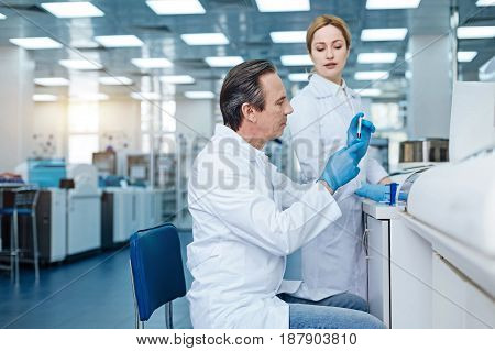 Modern lab. Delighted woman wearing white smock and keeping smile on face while looking downwards