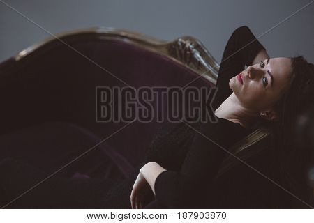 Beautiful Model In Stylish Dress Laying On Sofa