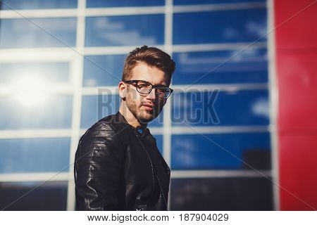 Stylish young man with glasses and a black leather jacket in the city