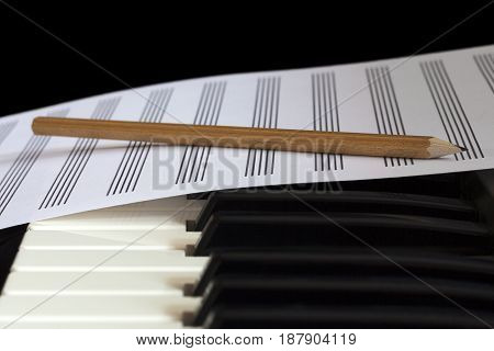 Piano keyboard and empty sheet with pencil, close-up