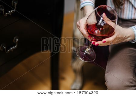 Female Hand Holding Glass Of Red Wine Closeup