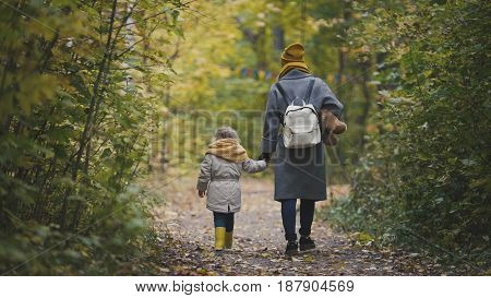 Young mother and her daughter little girl moving away in a autumn park, telephoto