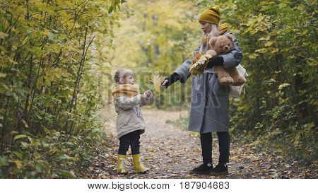 Mother and her daughter little girl walking in a autumn park - playing with Teddy Bear, telephoto