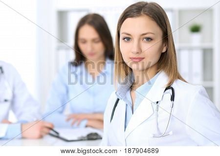 Young beautiful female doctor smiling  on the background with patient  in hospital. High level and quality medical service concept.