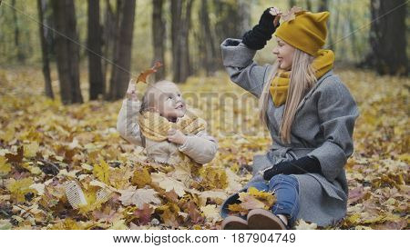 Happy family concept - little daughter with her mother plays with yellow leaves in autumn park, telephoto