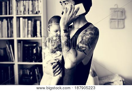 Daddy Talking Mobile Phone While Carrying His Baby