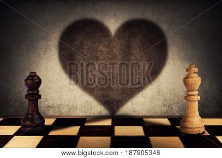 Black queen and white king chess pieces standing in front one another casting their shadows transform into a big heart on the wall. Love symbol impossible relationship togetherness concept.