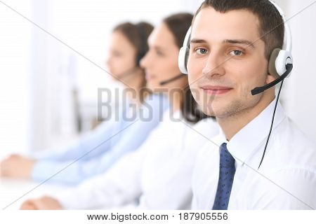 Call center operators. Focus at businessman in headset while consulting customers.