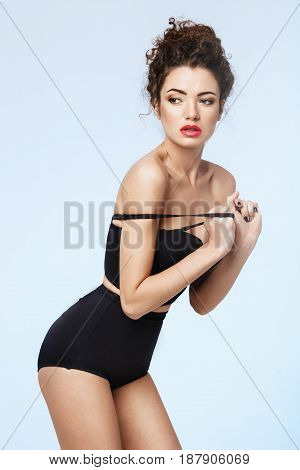 Beautiful model with red lips in black retro underwear posing over blue background. Copy space.
