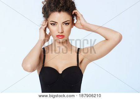 Beautiful model with bright make up posing looking at camera. Blue background. Copy space.