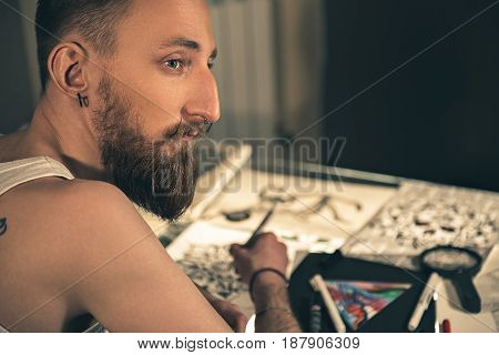 Focus on male expressing thoughtfulness. He drawing sketch of tattoos in salon