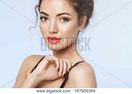 Close up photo of beautiful girl with bright makeup looking at camera. Blue background. Copy space.