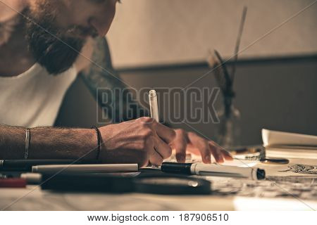 Focus on close up hand of calm bearded male painting picture. He sitting at table