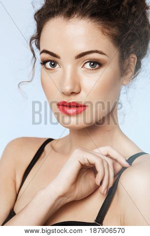 Close up portrait of beautiful girl with bright makeup looking at camera. Blue background.