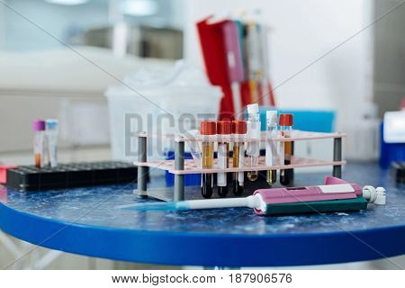 Checking blood. Blue table standing on the foreground, special medical dropper lying near support with test tubes