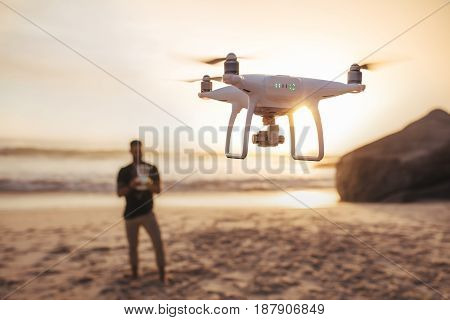 Drone being operated by a man standing in background on the beach. Young man on the sea shore flying a drone.