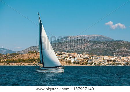 Sailing boat glides through water along the coast of Greek island. Luxury yacht and cruise holidays.