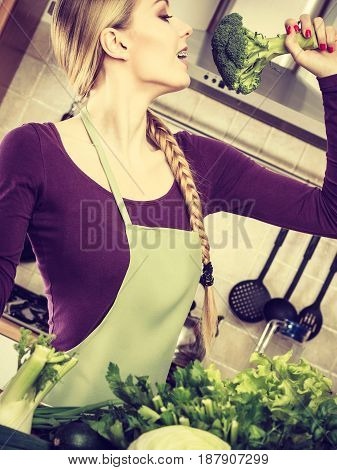 Woman In Kitchen With Green Vegetables Broccoli In Hand