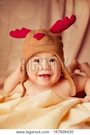 Happy smiling infant baby boy portrait dressed in christmas deer crocheted hat, winter holidays concept