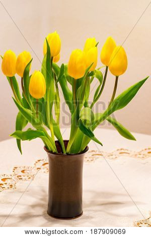 A tulip bouquet with many flowers as an Easter decoration in a brown flowerpot on a table with white tablecloth
