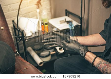 Focus on hands of man wearing gloves before creating picture on body of client