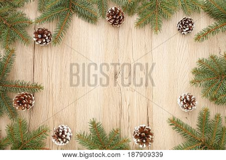 Christmas frame out of fir tree twigs and snowy pine cones on brown wooden background with lots of copy space.